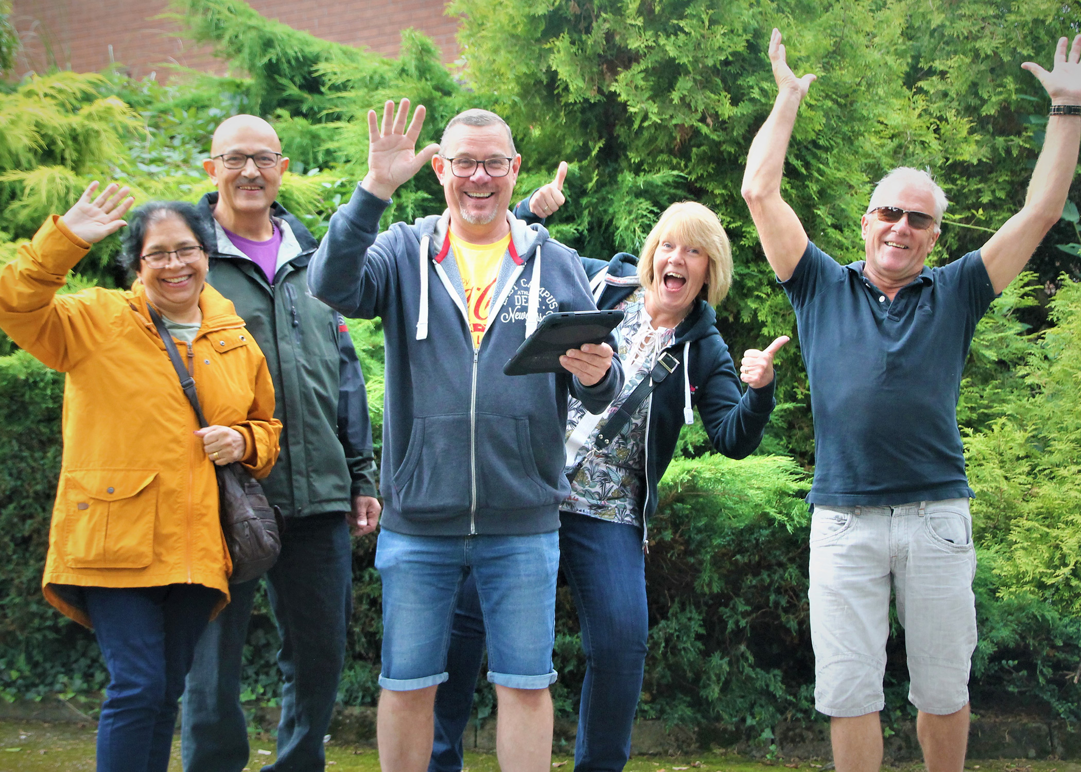Group of people smiling and waving whislt taking part in an iPad Treasure Hunt team building event
